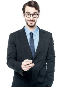 Young business man posing with mobile phone