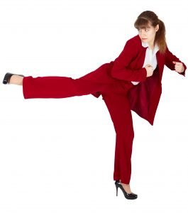 Young woman in a business suit kicks back