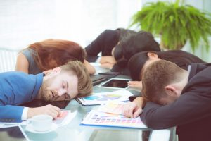 Bored business people sleeping in a meeting colleague.
