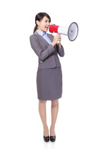 Business woman with megaphone yelling and screaming isolated on white background, asian model