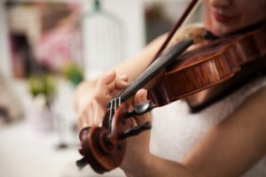 Girl playing the violin. Hand of a girl and a fiddle.