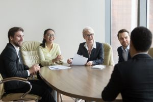 Multi ethnic hr managers laugh at funny joke of male applicant at job interview, diverse recruiters employers having fun talking to candidate make good first impression, hiring recruiting concept