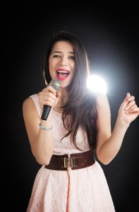 Female singer sings into a microphone on a black background