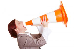 Angry business woman shouting in a big traffic cone