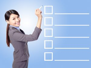 Beautiful business woman Filling Check list in the air (empty copy space great for your design) with blue background, asian model